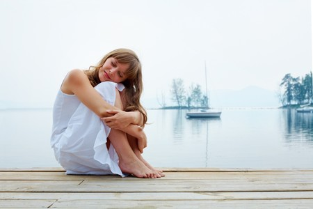 Portrait of pretty girl in white cotton clothes having rest by the seaside photo