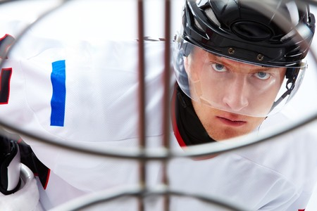 Portrait of hockey player looking at adversary before making goal  photo
