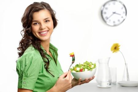 woman clock: Retrato de una ni�a mirando positiva y sosteniendo una bawl con ensalada  Foto de archivo