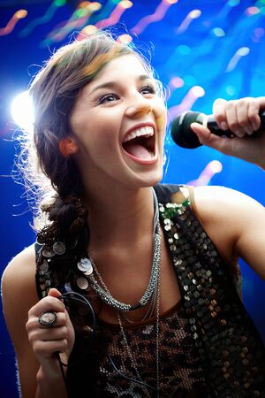 cantando: Retrato de una niña glamorosa sosteniendo un micrófono y cantando