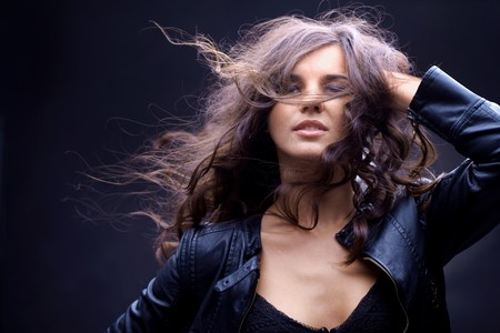 Portrait of a girl with streaming hair against black background  photo