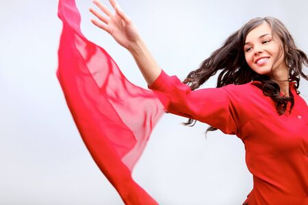A girl in red throwing red fabric photo
