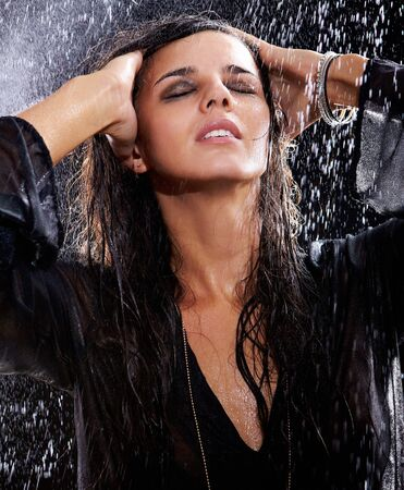 Portrait of a young brunette in black posing in rain   photo