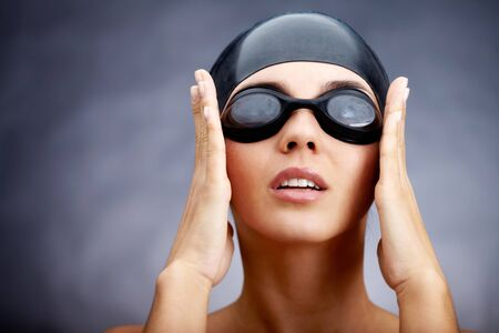 swim goggles: Portrait of a young woman in goggles and swimming cap Stock Photo