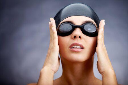 swim goggles: Retrato de una mujer joven en gafas y gorra de nataci�n