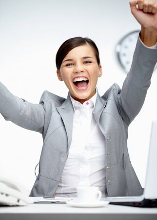 gladness: Image of young businesswoman shouting in gladness with raised arms