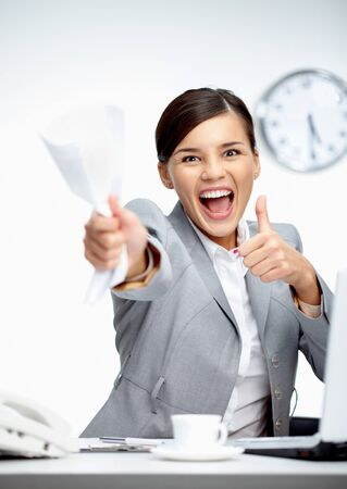 Image of young businesswoman with crumbled paper showing thumbs up photo