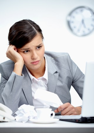 Image of young employer looking at laptop with troubled expression photo