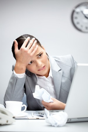Image of young employer looking at laptop with anxiety photo
