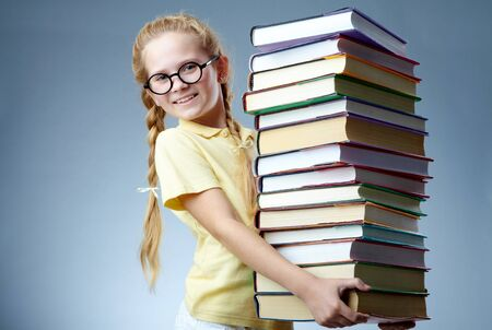 culture school: Image of happy schoolgirl with stack of books looking at camera