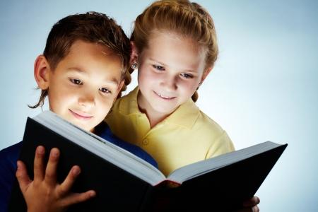 Image of smart children reading interesting book photo