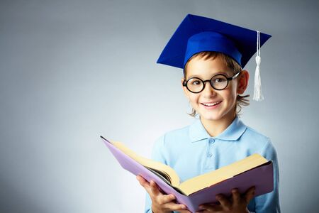 lad: Portrait of cute lad in eyeglasses and student hat holding open book