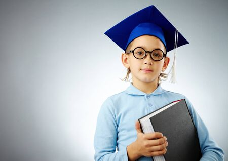 Portrait of cute lad in eyeglasses and student hat with book looking at camera Stock Photo - 8062475