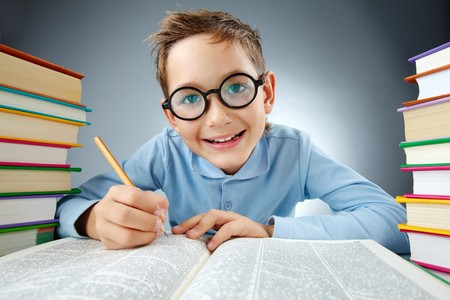 one little boy: Portrait of cute lad in eyeglasses making notes in book during reading