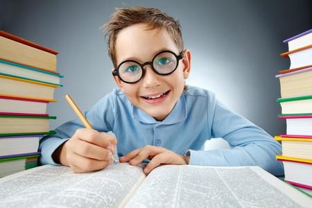 Portret van schattige jongen in bril maken van aantekeningen in boek tijdens lezing