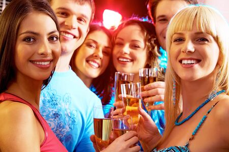 people partying: Portrait of happy young people holding glasses of champagne  Stock Photo