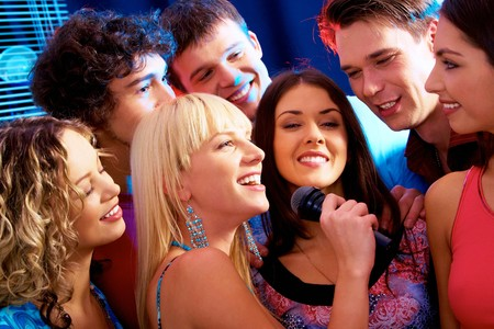 Image of happy young woman sings a song in the environment of her friends  photo