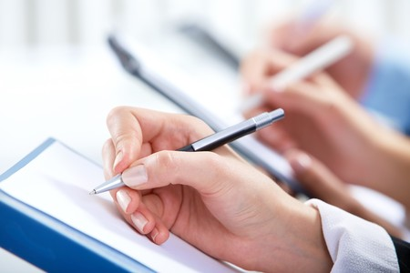 meeting place: Image of human hand writing on paper at seminar or conference Stock Photo
