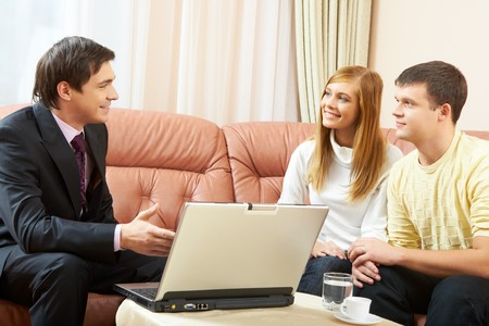 Portrait of a businessman interacting with young couple photo