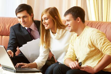 Portrait of a businessman and young couple looking at something in laptop photo