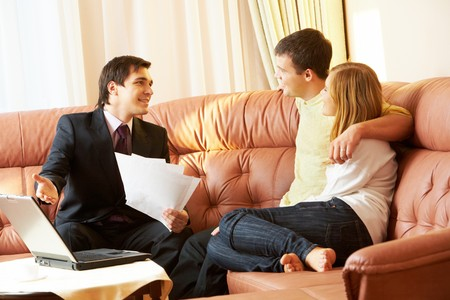 Portrait of a businessman with papers explaining something to young couple photo