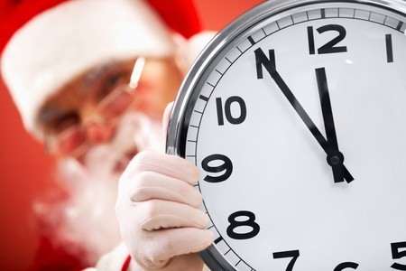 clock showing five minutes to midnight with Santa on background photo