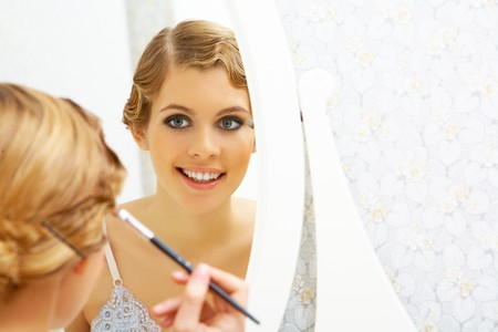 Image of pretty female looking in mirror and doing makeup Stock Photo - 8140632