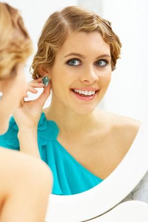 aretes: Imagen de bastante femenino de mirar en el espejo y poniendo en aretes  Foto de archivo