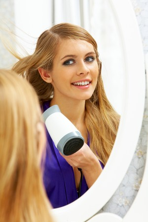 Image of pretty female looking in mirror while drying her hair photo