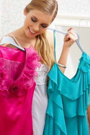 choosing selecting: Image of pretty female looking at smart dresses while choosing a right one