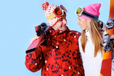 Portrait of happy couple with skis in hands looking at each other and smiling photo