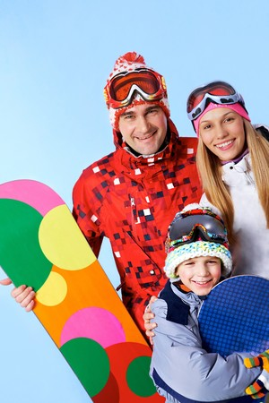Portrait of happy family with snowboards looking at camera on blue background photo