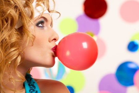 Profile of gorgeous female blowing chewing gum on colorful background photo