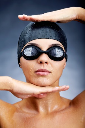 Portrait of a young woman posing in goggles and swimming cap photo
