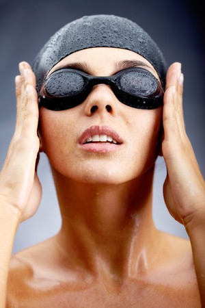 swim goggles: Portrait of girl in goggles and swimming cap posing before camera