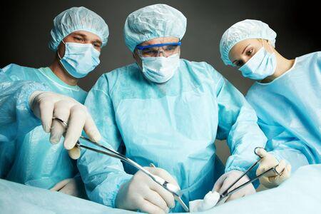 cirujano: Tres cirujanos que trabajan la operaci�n contra el fondo oscuro  Foto de archivo