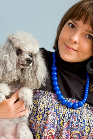 Photo of grey poodle with its master in studio  photo