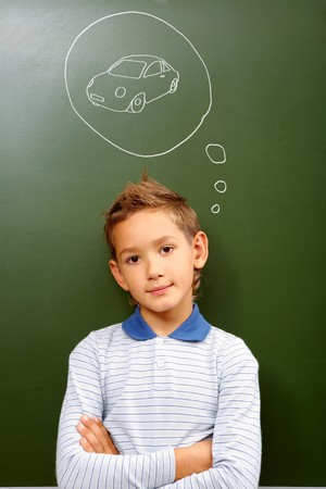 lad: Portrait of smart lad by the blackboard thinking of car and looking at camera