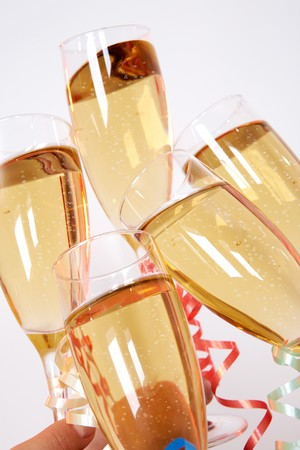 toasting wine: Close-up of flutes of golden champagne being clinked during toast Stock Photo