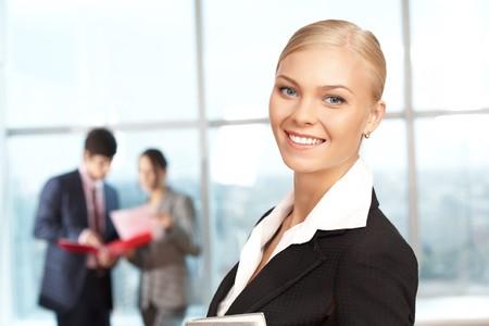 Portrait de femme d'affaires heureux, souriant à la caméra sur fond de travailleurs