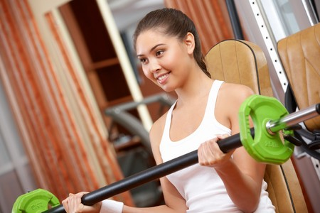 Photo of active girl lifting dumbbell - building muscle photo