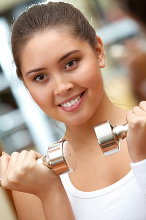 Portrait of young female with dumbbells doing exercises in gym Stock Photo - 8225962