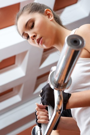 pumping: Photo of active girl pumping muscles on special equipment