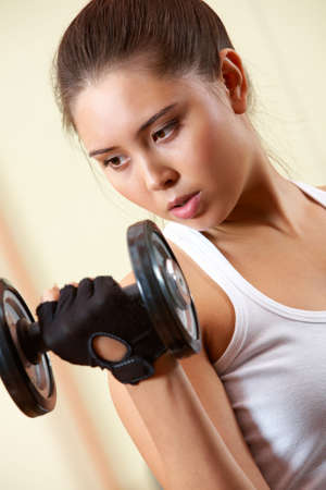 Portrait of young female doing exercises with barbell in gym Stock Photo - 8226517