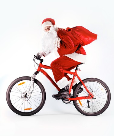 adult christmas: Photo of happy Santa Claus with red sack riding bike