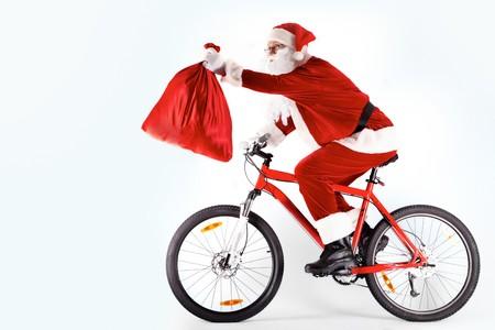 papa noel: Foto de feliz Santa Claus en bicicleta con saco rojo en el brazo estirado  Foto de archivo