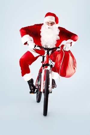 Photo of happy Santa Claus with red sack on bike photo