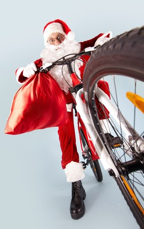 Photo of amazed Santa Claus with red sack on bike Stock Photo