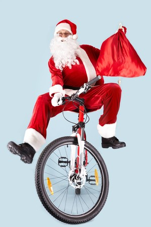 Photo of joyful Santa Claus with red sack on bike looking at camera