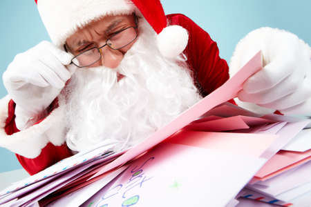 Image of Santa Claus in front of heap of letters reading one of them photo